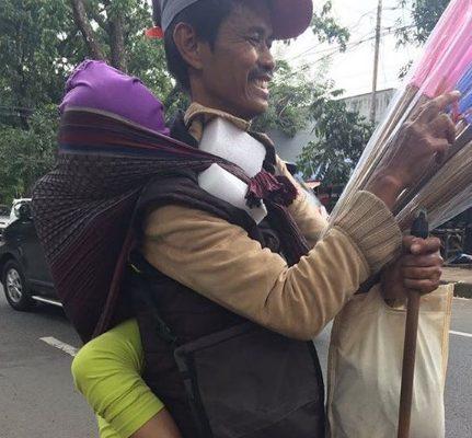 Sambil Gendong Anaknya yang Lumpuh, Pria Ini Jualan Sapu Lidi Keliling Bandung